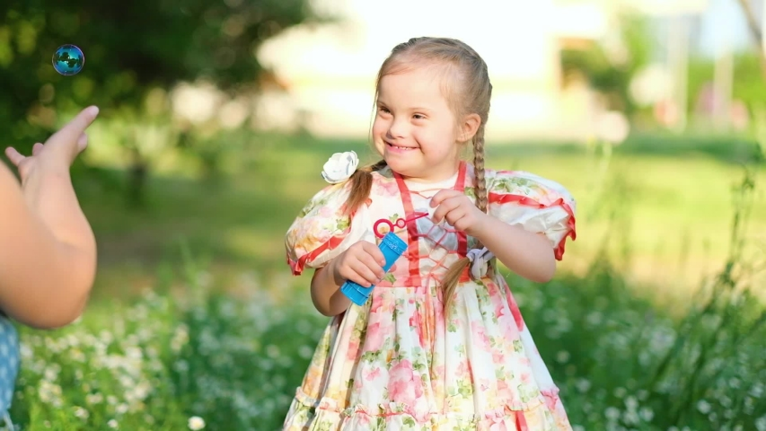 A girl with Down syndrome blows bubbles with mother. The daily life of a child with disabilities. Chromosomal genetic disorder in a child. Royalty-Free Stock Footage #1054539728