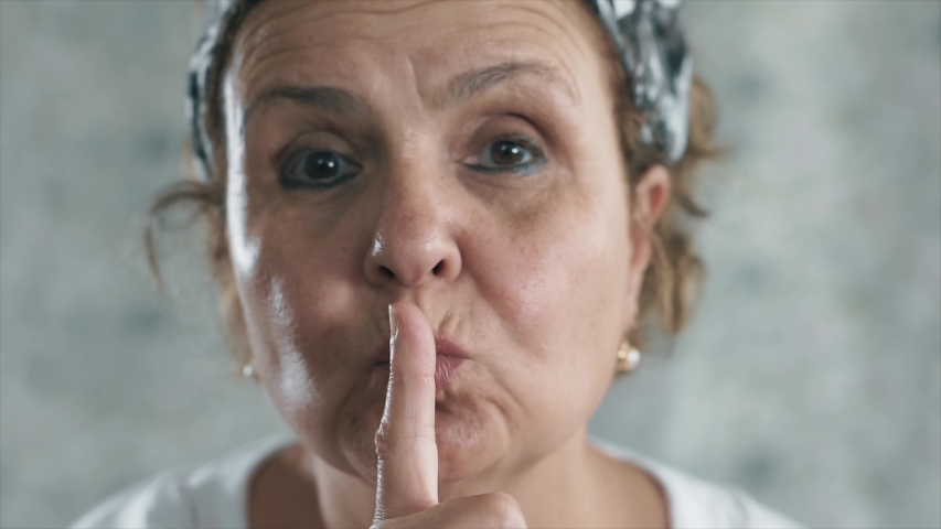 Old woman hush signing, shh concept. Her finger on her lips. Silence elderly woman face portrait.    Shutterstock HD Video #1054539803