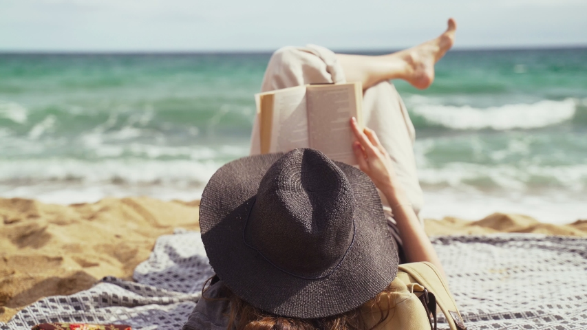 On the beach. A girl in a black hat lies on the beach and reads a book. Light breeze. Turquoise waves in the background. Summer chill. Vacation at the sea. Rest and pleasure. Holidays on the beach. | Shutterstock HD Video #1054540718