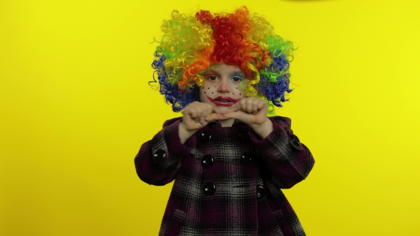 Little caucasian child girl clown in rainbow wig making silly faces. Five years old female kid having fun, smiling, dancing, looking at camera. Expressions. Copy space. Halloween. Yellow background   Shutterstock HD Video #1054541942