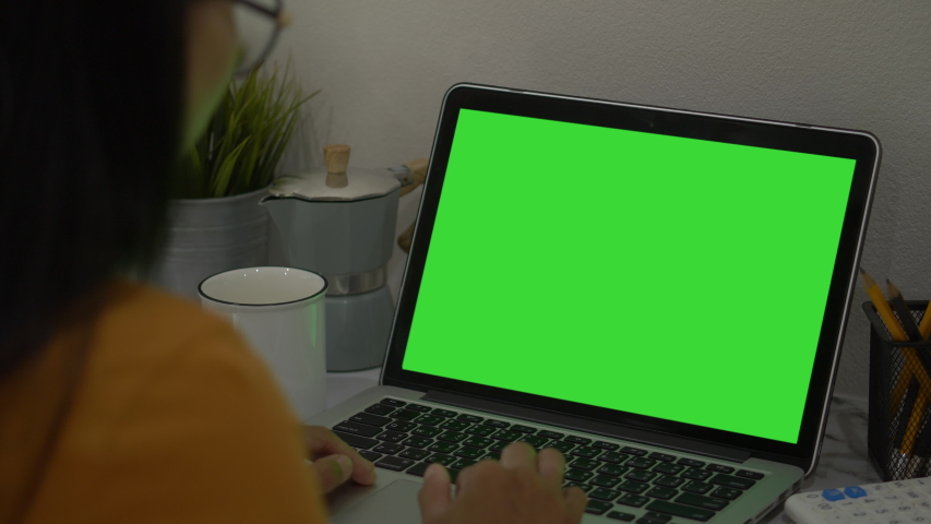 Over the shoulder shot of a business woman working in office interior on pc on desk, looking at green screen. Office person using laptop computer with laptop green screen, Royalty-Free Stock Footage #1054542539