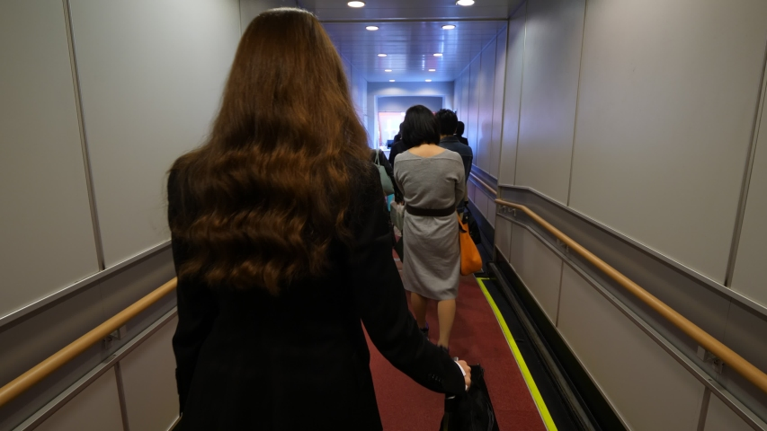 Passengers boarding to plane, people slowly walk, economy class queue at jet bridge. Woman go at end of line with trolley case, first person view camera follow behind | Shutterstock HD Video #1054546073