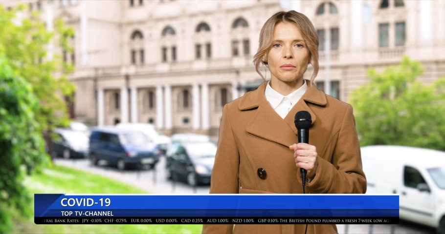 Caucasian female journalist talking in microphone about covid-19 while being on air in news from city street. Woman newscaster with mic at TV news in episode. Coronavirus pandemic. | Shutterstock HD Video #1054549055