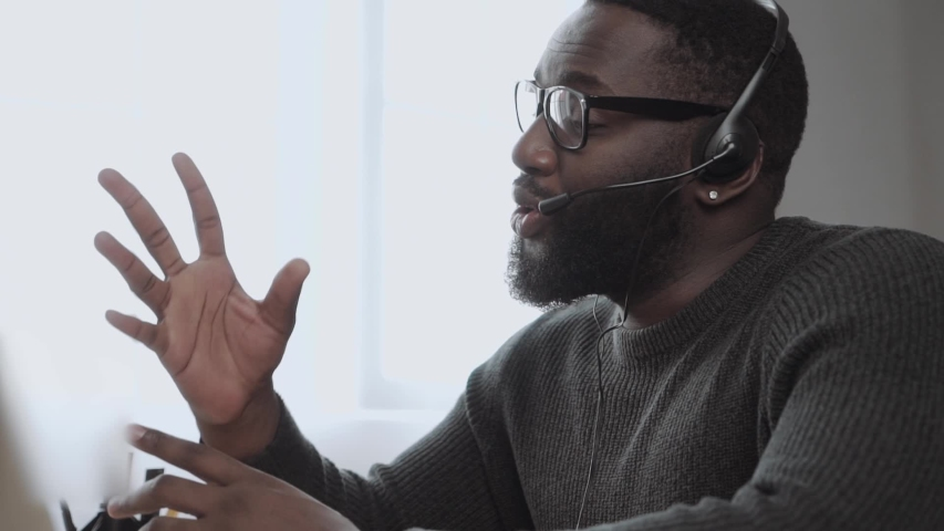 African American male, call center agent in headset consult business client online using laptop \ black man in headphones leads an online webinar Royalty-Free Stock Footage #1054549661