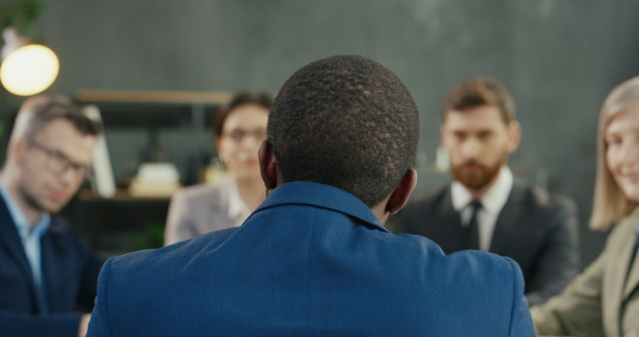 Rear of male boss sitting at table with company business colleagues at meeting and discussion of work. Back view on African American man running conference of partners and investors at desk in office. Royalty-Free Stock Footage #1054550057