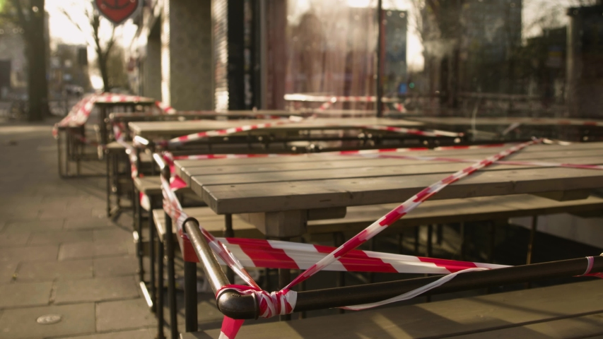 Outdoor restaurant tables with barricade tape in Hamburg Germany during the coronavirus lockdown. Royalty-Free Stock Footage #1054550207