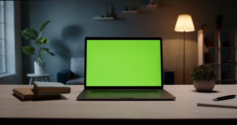 Close up shot of modern chroma key green screen laptop computer set up for work on desk at night - remote work, technology concept 4k video template Royalty-Free Stock Footage #1054550474