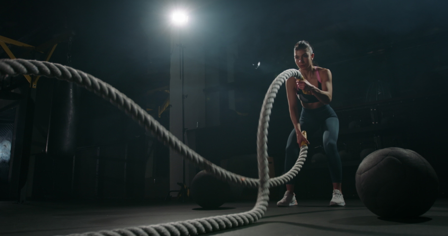 Active dedicated motivated female athlete training in gym with battle ropes, determined confident girl enjoying bodybuilding achieving goals with healthy lifestyle 4k footage Royalty-Free Stock Footage #1054550504