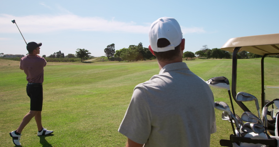 Caucasian male golfers standing on a golf course wearing golf clothes, one swinging a golf club and hitting the ball, while his opponent stands nearby in the foreground, with clubs in a golf buggy Royalty-Free Stock Footage #1054550816