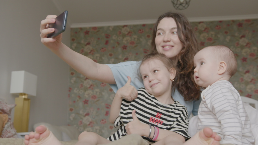 Young Mother and Two Daughters, Preschooler and Infant, Make Selfie with Smartphone, Lying on a Bed. Cozy Home Interior. Royalty-Free Stock Footage #1054552028