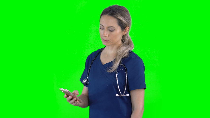 4K portrait of female nurse doctor on green screen isolated with chroma key. Woman standing using smartphone. Side view