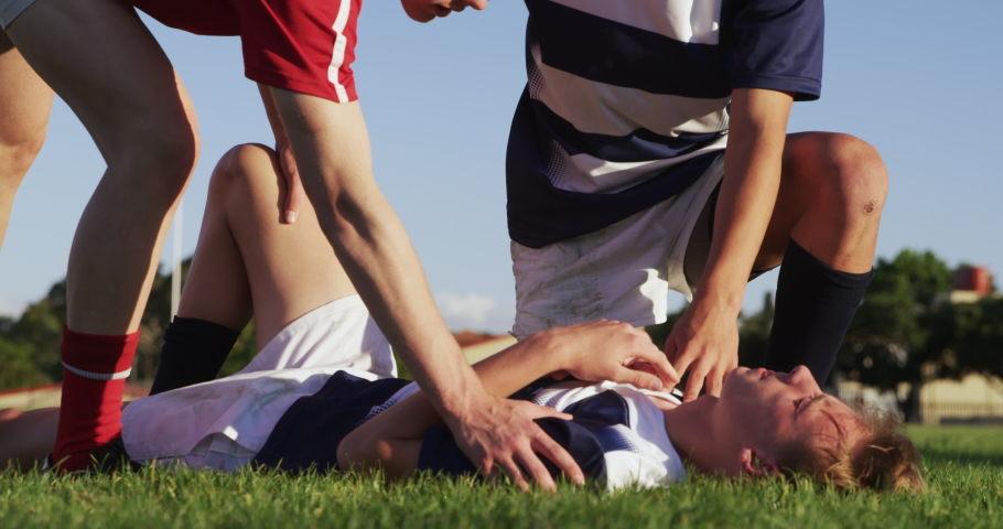 Side view of two Caucasian teenage male rugby players helping another Caucasian teenage male rugby player from the other team with help from his teammate during a rugby match in slow motion | Shutterstock HD Video #1054559339