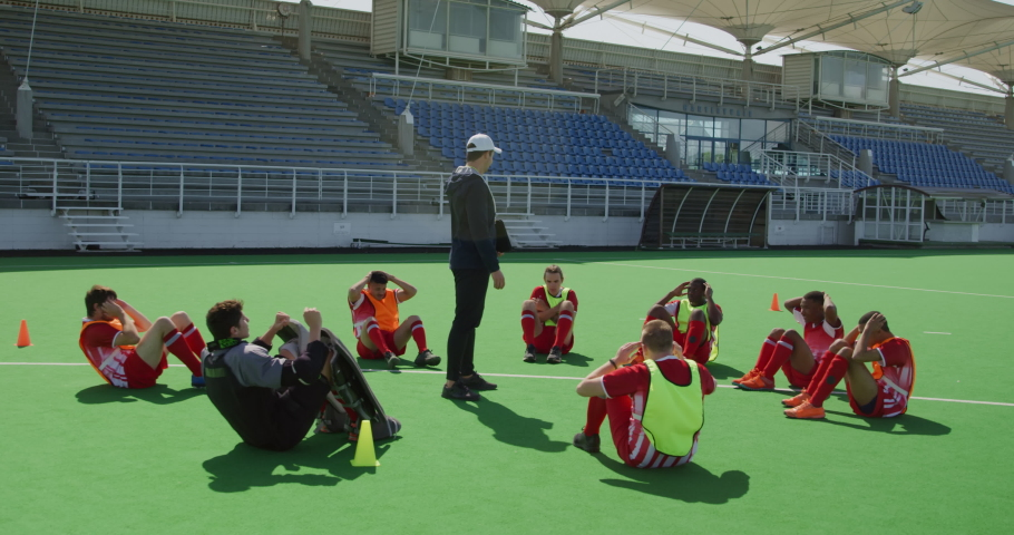 Side view of a multi-ethnic group of teenage male field hockey players and their Caucasian male field hokey coach training, doing sit ups in a circle while the coach stands watching, in slow motion | Shutterstock HD Video #1054559792