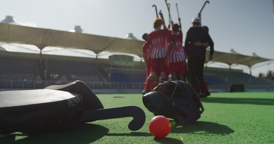Close up detail of a field hockey equipment, lying on a field hockey pitch, with a multi-ethnic team of field hockey players raising hockey sticks together in the background, in slow motion | Shutterstock HD Video #1054560083