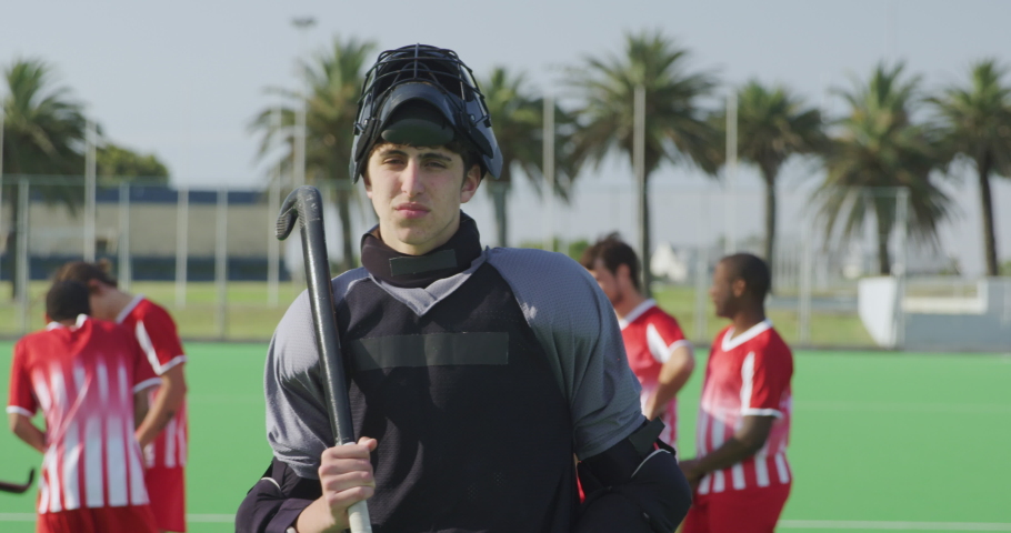 Front view of a Caucasian male teenage field hockey goalkeeper, standing on a field hockey pitch, turning to camera and looking at it, with his teammates in the background, in slow motion | Shutterstock HD Video #1054560140