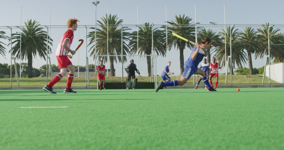 Side view of two multi-ethnic teenage male field hockey teams, playing a field hockey game, with one of the players hitting the ball with a hockey stick and goalkeeper defending the shot with his leg | Shutterstock HD Video #1054560323
