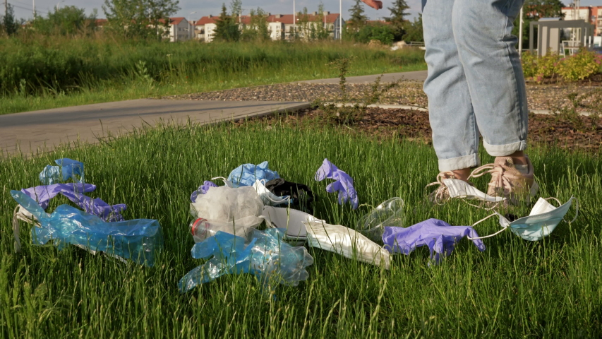 Volunteer collects trash in a blue bag. Tons of garbage was added during the COVID-19 pandemic. | Shutterstock HD Video #1054561424