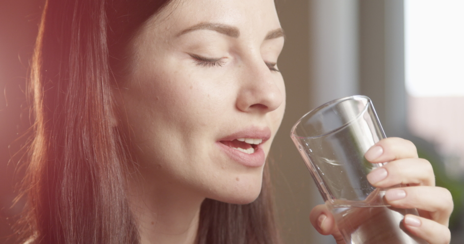 Thirsty Woman Drinking Water from a Glass Indoors with Sun Shining a Close up Shot on Red Camera   Shutterstock HD Video #1054561460