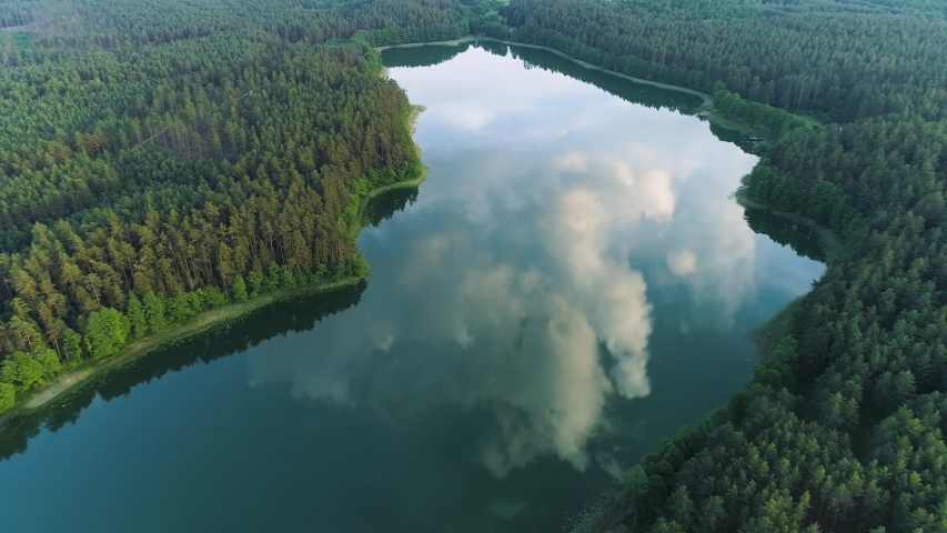 Beautiful landscape in aerial drone shot. Forest woods and calm tranquil lake. Fat white clouds mirroring on water surface.   Shutterstock HD Video #1054562048