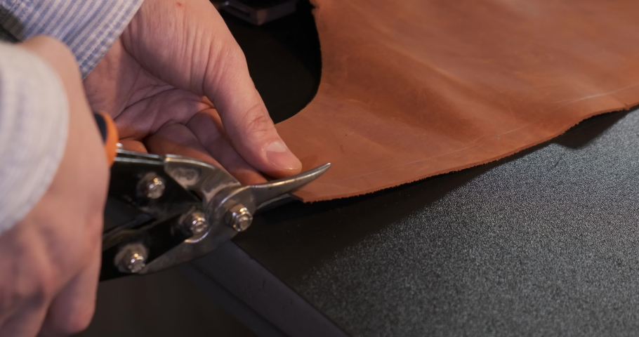 Man Using Scissors Cut Brown Leather Sheet, Leather Craftsman Creates Product with his Hands, Leather Making Process in Home Office. Small Business at Leather Industry. Production of Designer Clothes