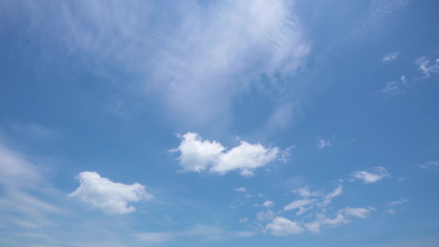 Light white clouds fly across a bright blue sky. Clear sky at sunny summer afternoon. Spring cloudscape background. Copy space Royalty-Free Stock Footage #1054567055