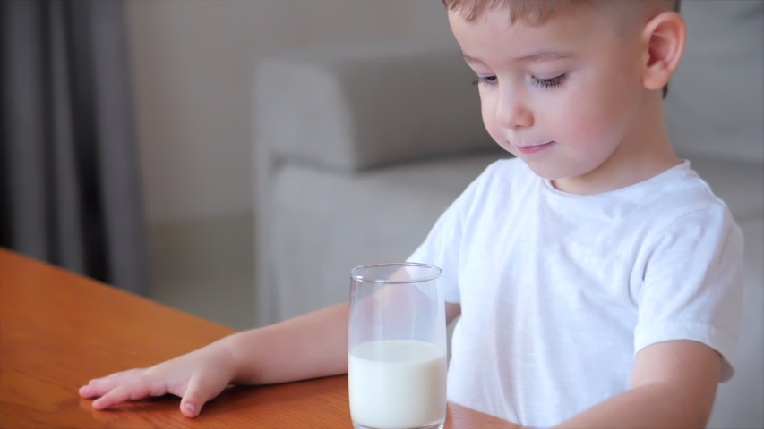 Cute baby boy drinking a glass of Milk sitting on the couch at home. Slow motion little boy drinking water. Close-up. Portrait Funny little Child is drinking a cup of water.