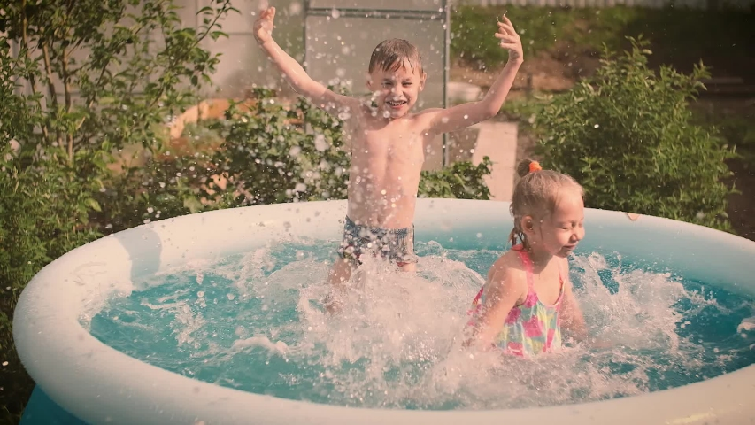 Children bathe and frolic in the pool in the summer, splashing water, lifestyle design. Activity nature leisure. Slow motion. | Shutterstock HD Video #1054574957