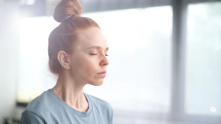 Close-up face of pretty redhead young woman doing breathing yogic practices at home office. Girl with closed eyes meditating on background of large window. Cute lady is making deep breath-exhalation. Royalty-Free Stock Footage #1054575686