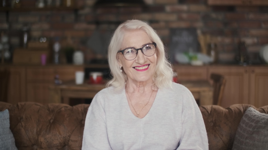 Elderly, beautiful woman with gray hair smiling looking at the camera. Portrait of a 70 year old grandmother with glasses. Happy senior citizen. An elderly, business woman sits on a sofa while being