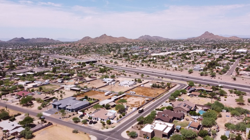 Phoenix Arizona, USA community  aerial drone view of North Phoenix  neighborhood, housing and Interstate 51, Piestewa freeway with  mountains in background