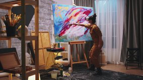 Female painter working on abstract painting in studio. Modern artwork paint on canvas, creative, contemporary and successful fine art artist drawing masterpiece