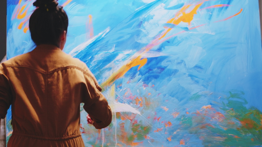 Innovative female painter using orange paint on big canvas.  Modern artwork paint on canvas, creative, contemporary and successful fine art artist drawing masterpiece | Shutterstock HD Video #1054578155