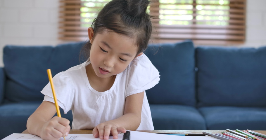 Cheerful asian cute small kid girl artist playing alone drawing coloring picture with pencils, focused smart preschool child enjoying creative art hobby activity at home, children development concept.   Shutterstock HD Video #1054580450