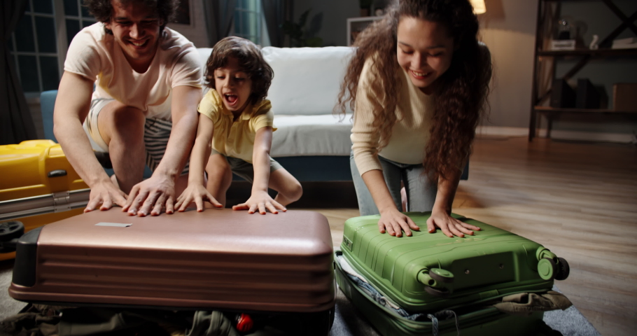 Funny asian family of three is preparing for their travel adventure, packing clothes into suitcase, getting ready for road trip - travelling, happy family concept 4k footage   Shutterstock HD Video #1054581929