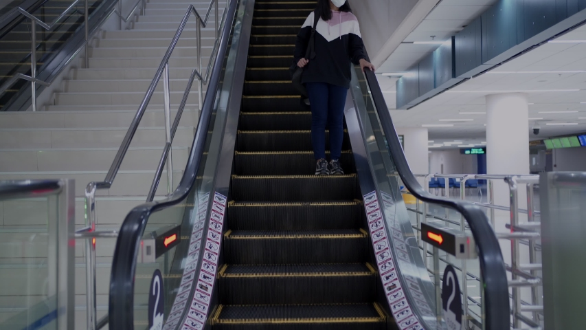 Asian woman in white mask coming down form escalator at shopping mall, travel moving covid-19 pandemic, new normal social distance, female in mask walk down escalator, indoor building, public place | Shutterstock HD Video #1054584119