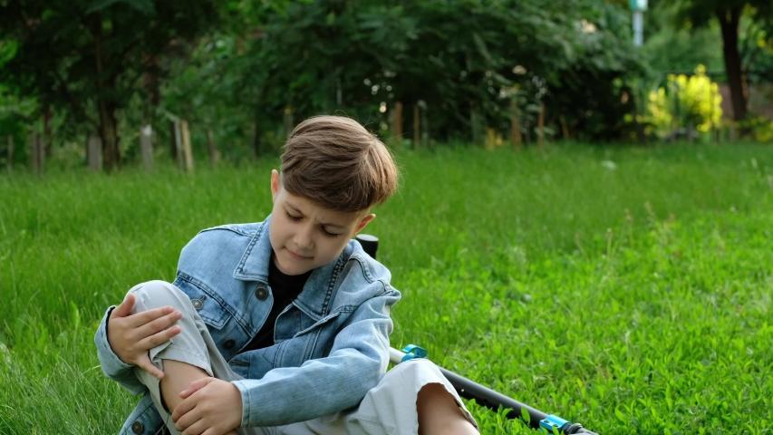 Child fell off scooter. Little boy is suffering from pain of falling off bike. | Shutterstock HD Video #1054588850