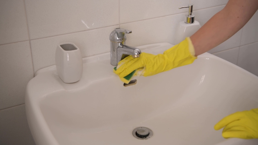 Woman hands in the work gloves cleans the bathroom, washes a washbasin   Shutterstock HD Video #1054592087