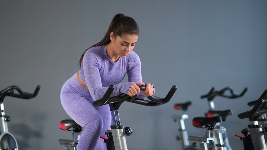 A beautiful athletic young brunette woman in sportswear trains on a sycle in the gym against the backdrop of a gray wall.   Shutterstock HD Video #1054594697