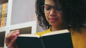 Close up view of Calm african attractive woman in eyeglasses reading book while sitting on the floor indoors