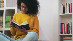 Calm african attractive woman in eyeglasses reading book while sitting on the floor indoors