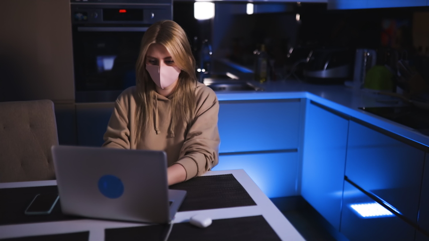 Serious young woman works at laptop wearing pink face mask late at night | Shutterstock HD Video #1054598963