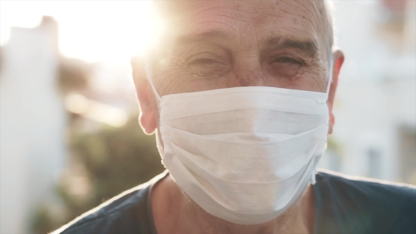Senior old man is wearing face mask in outdoor. Sun light, flare and elderly senior guy is protecting himself from coronavirus, covid-19 | Shutterstock HD Video #1054599167