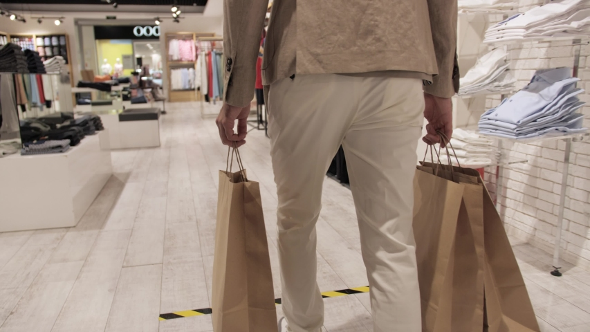 Satisfied client after shopping with a bag in his hands leaves the store of branded clothing Royalty-Free Stock Footage #1054599845