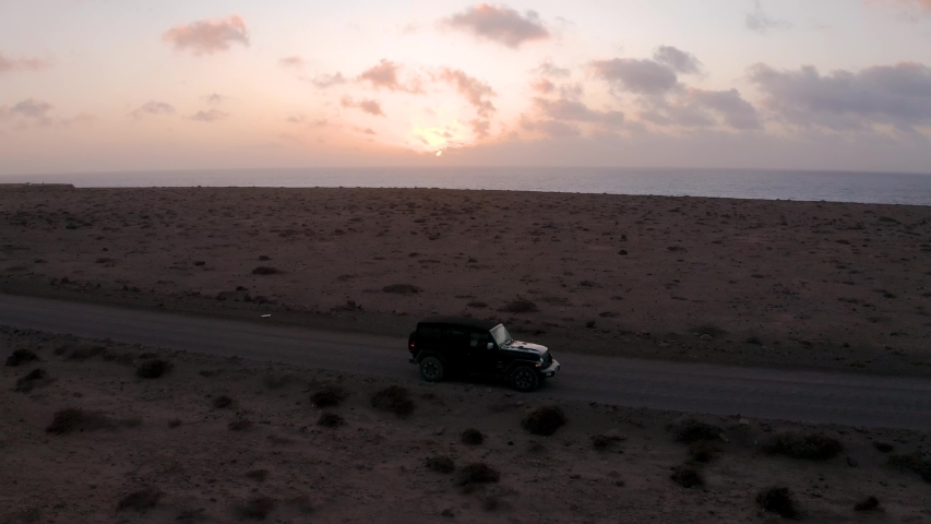 Aerial of Jeep driving off-road during sunset in Fuerteventura, Spain | Shutterstock HD Video #1054601654
