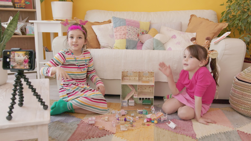 Shooting a Video Blog for Children with Smartphone on Tripod. Production of Kid's Content. Two Cute Cheerful Little Caucasian Girls Playing with a Doll's House, Talking and Laughing.  Royalty-Free Stock Footage #1054602764