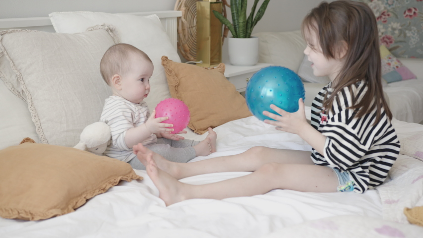 Close-Up Portrait of Two Little Sibling Baby Girls Sitting on a Bed, Playing with Blue Rubber Ball Royalty-Free Stock Footage #1054602797