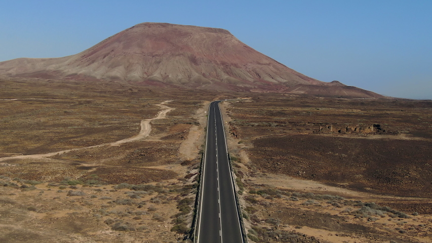 Spain, Canary Islands, Fuerteventura, Montana Roja and road leading to Corralejo Dunes Natural Park | Shutterstock HD Video #1054603421
