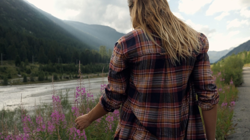 Woman wandering in flower field by the river enjoying nature touching with hands the spring blossoms. People simple life enjoying outdoor  Royalty-Free Stock Footage #1054604207