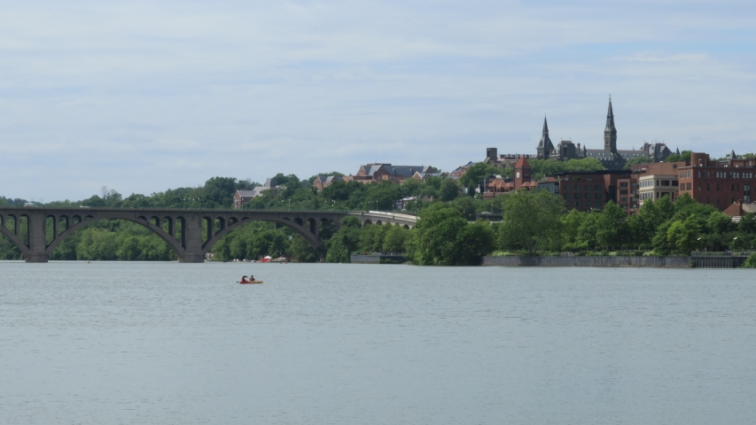 Two people paddle in a tandem kayak on the Potomac river in Washington, D.C.. Key Bridge and the Georgetown skyline are seen the background.