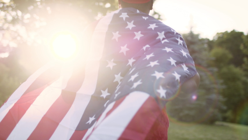 Joyful african american woman running with the American flag blowing in the wind. Independence day celebration. Shot in slow-motion in 4k.  Royalty-Free Stock Footage #1054606493